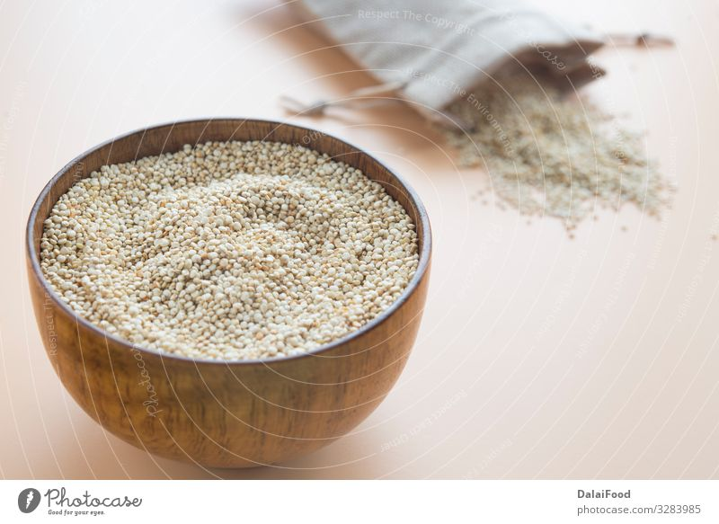 Uncooked Quinoa in wooden bowl with textil bag Nutrition Bowl Wood Diet Chenopodium background Cooking brown background Cereal copy space text food free gluten