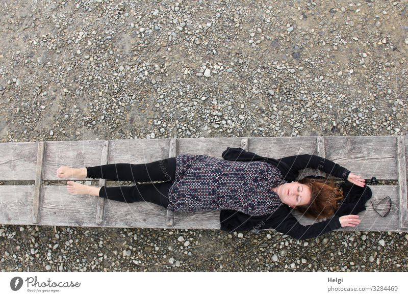 a clothed woman with dark and patterned clothing lies with closed eyes on a jetty Human being Feminine Woman Adults 1 45 - 60 years Environment Nature Spring