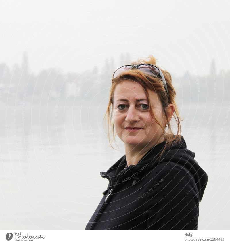 Portrait of a smiling woman with long brunette hair and dark jacket in a foggy landscape Human being Feminine Woman Adults 1 45 - 60 years Fog Lake Clothing