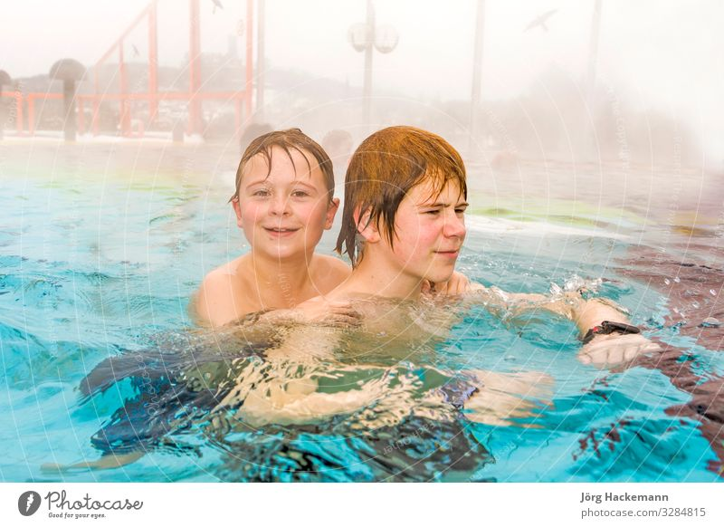 brothers are swimming in the thermic pool in Wintertime Joy Happy Spa Swimming pool Leisure and hobbies Playing Sports Human being Friendship Fog Warmth