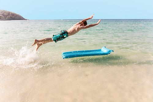 boy with red hair is enjoying jumping on the air mattress Joy Vacation & Travel Beach Ocean Island Waves Boy (child) Youth (Young adults) Sky Jump Cute Speed
