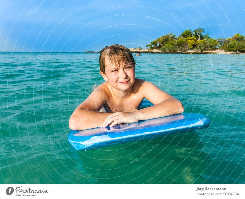 boy is swimming on his surfboard Joy Happy Relaxation Vacation & Travel Beach Ocean Island Child Youth (Young adults) Nature Landscape Sky Horizon Warmth