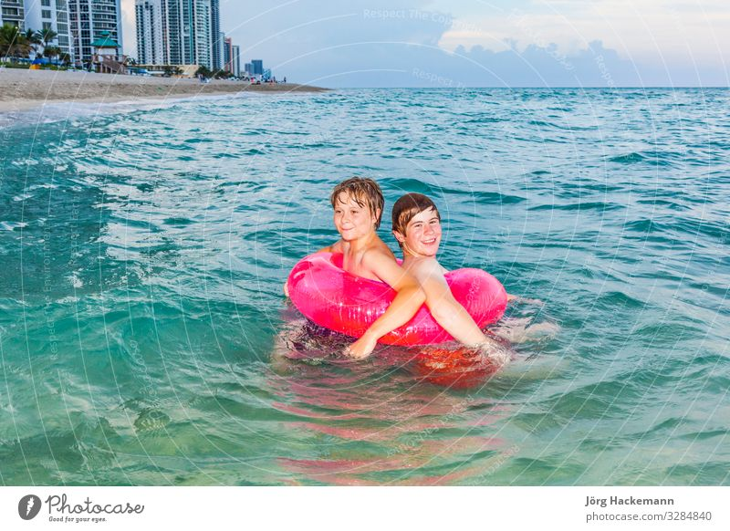 brothers in a swim ring have fun in the ocean Child Vacation & Travel Nature Youth (Young adults) Beautiful Sun Ocean Relaxation Joy Warmth Happy Boy (child)