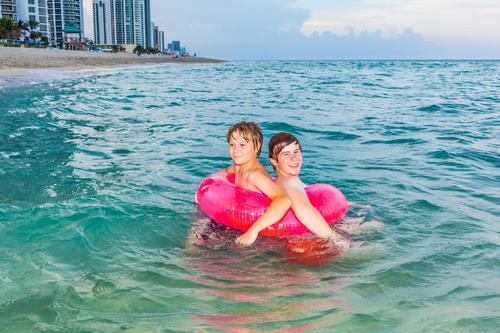 brothers in a swim ring have fun in the ocean Joy Happy Beautiful Skin Relaxation Leisure and hobbies Vacation & Travel Sun Ocean Waves Child Boy (child)