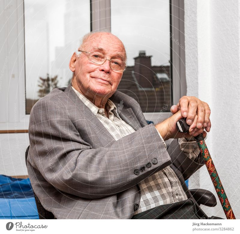 smiling senior man sits at the chair Lifestyle Joy Happy Face Relaxation Calm Chair Retirement Human being Man Adults Jacket Old Smiling Sit Smart Gray Wisdom