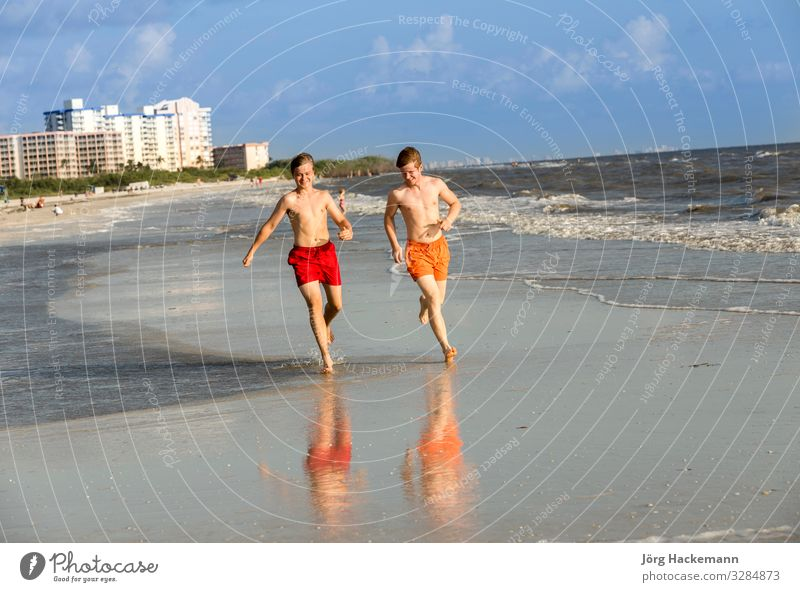 teenager enjoys jogging along the beach Vacation & Travel Youth (Young adults) Relaxation Joy Beach Movement Laughter Happy Boy (child) Sand Body Smiling