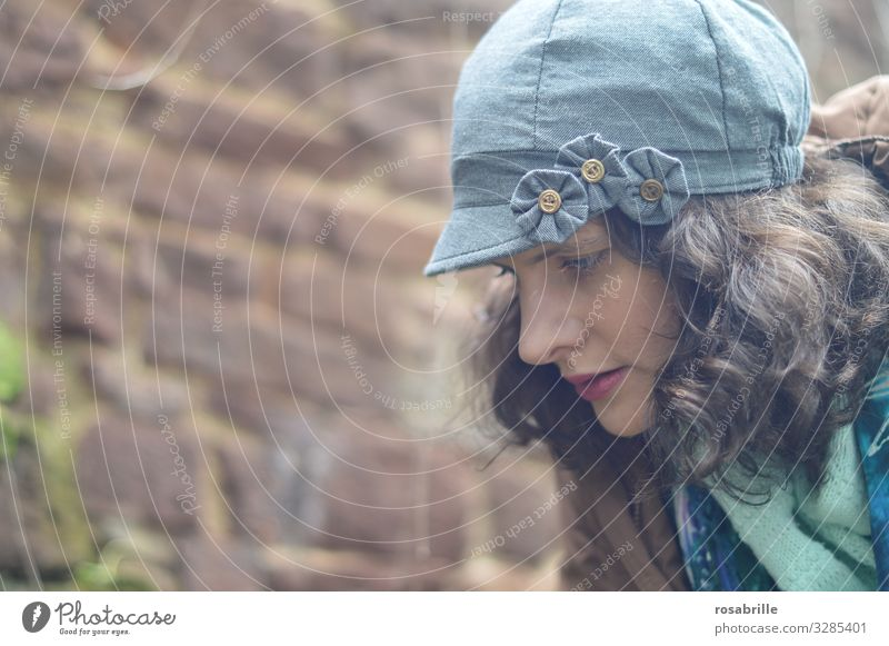 young, pretty, curly, brunette woman with hat, jacket and scarf in profile looks down thoughtfully Woman Brunette youthful Curl Curly Meditative Think brood