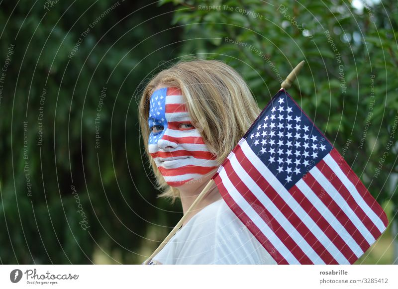Showing the flag | literally | patriotic young blonde woman with American flag and flag painted on her face outdoors hoping for the victory of her soccer team