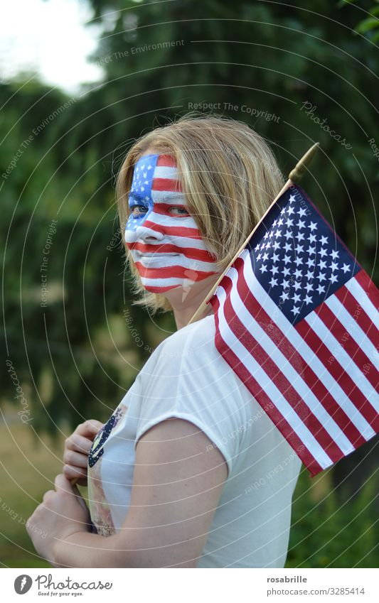 Show your colours | literally | patriotic young blonde woman with American flag and banner painted on her face outdoors hoping for the victory of her soccer team