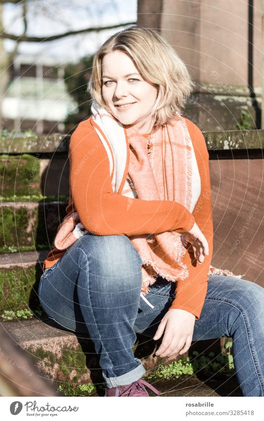 Portrait of young pretty blonde woman in jeans with orange sweater and scarf on stairs in full sunlight Woman Blonde youthful Bob hairstyle Scarf Autumn Day
