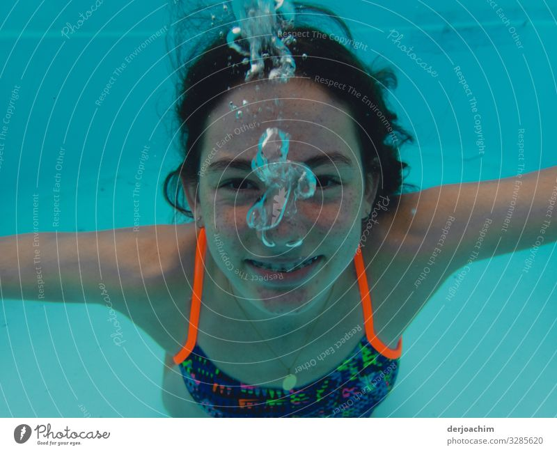 A girl under water looks at the photographer. She laughs and it goes blub blub.... Joy Athletic Life Swimming pool Aquatics Swimming & Bathing Girl