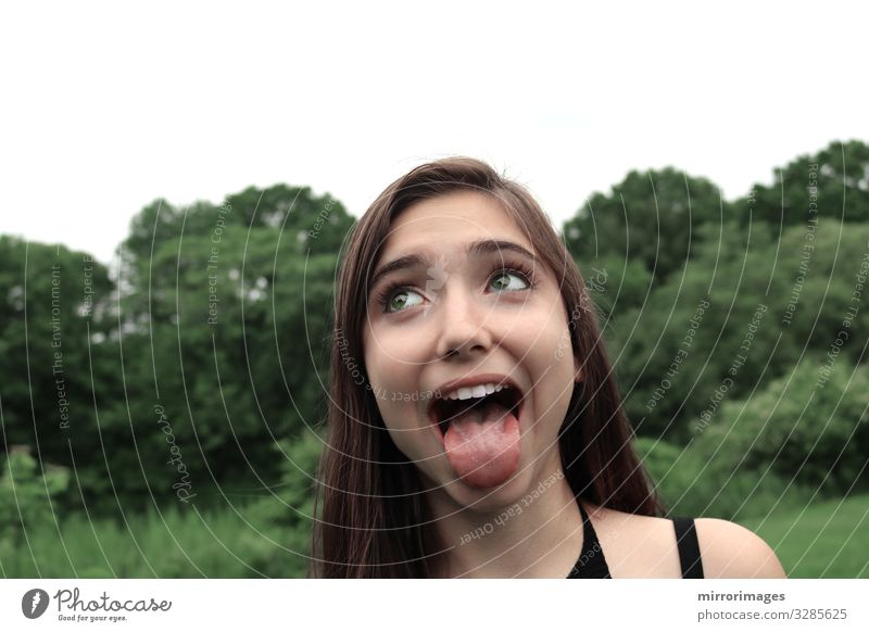 young woman in a park with open mouth and tongue out Lifestyle Beautiful Young woman Youth (Young adults) Woman Adults 13 - 18 years 18 - 30 years Laughter