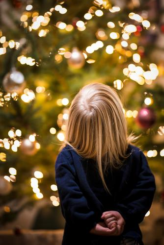 Child stands in awe before a Christmas tree reverence Joy Enthusiasm Anticipation Cute Belief Santa Claus Girl Fairy lights corona