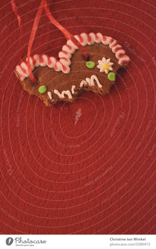 bite into gingerbread heart on red background Food Dough Baked goods Gingerbread heart Nutrition Kitsch Odds and ends Souvenir Heart Happiness Hip & trendy