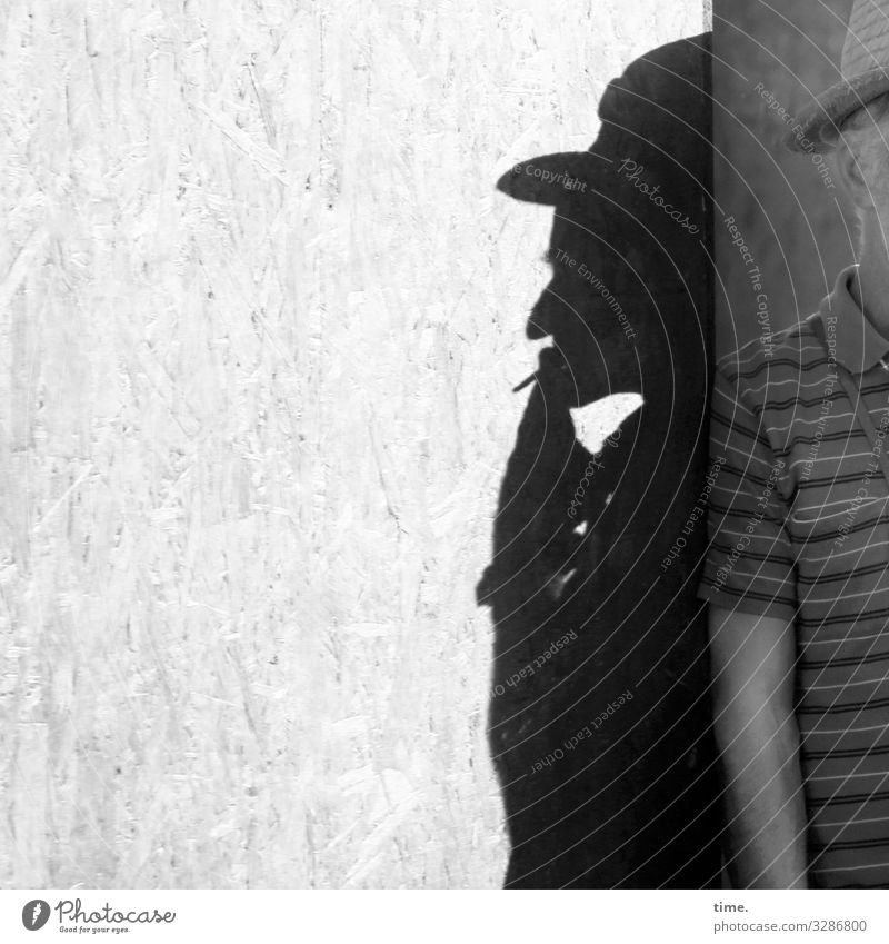hidden track Masculine Man Adults 1 Human being Wall (barrier) Wall (building) Hoarding Board Corner T-shirt Hat Observe Relaxation To hold on Smoking Stand