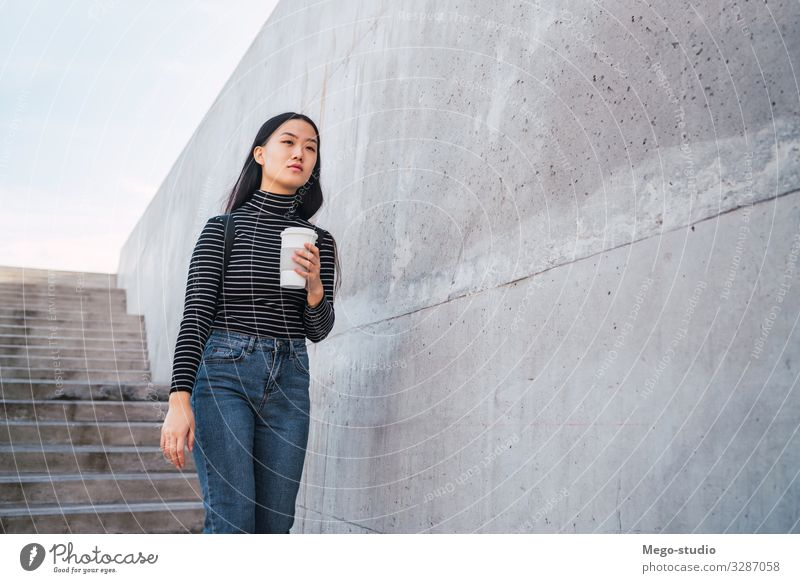 Asian woman holding a cup of coffee. Drinking Coffee Lifestyle Style Happy Beautiful Profession Human being Woman Adults Street Brunette Going Smiling Modern