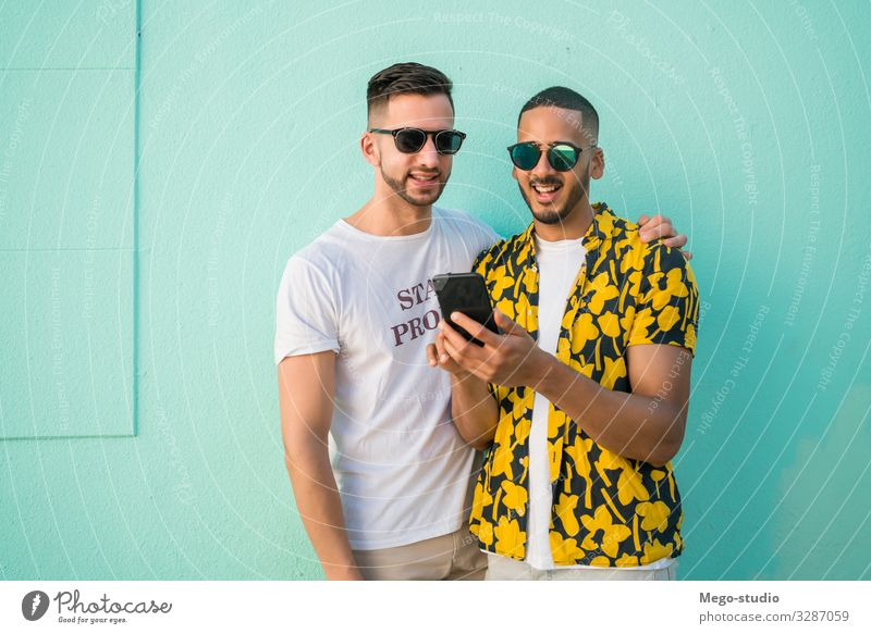 Gay couple spending time together while using phone. Lifestyle Happy Leisure and hobbies Freedom Cellphone PDA Homosexual Man Adults Couple Love Happiness