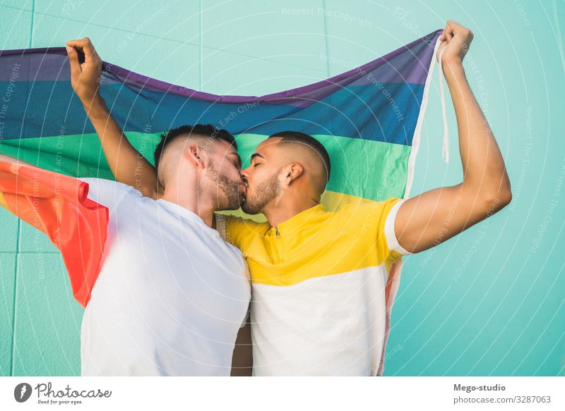 Gay couple embracing and showing their love with rainbow flag. Lifestyle Happy Freedom Feasts & Celebrations Human being Homosexual Man Adults Couple Partner