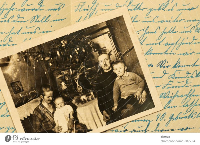 an old paper painting from the 1920s shows a family with two small children in front of a decorated Christmas tree - lying on an old document in old German handwriting