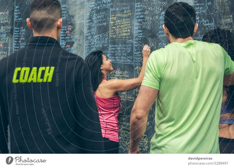 Athlete woman writing down results on the gym blackboard Lifestyle Sports Blackboard Student Human being Woman Adults Man Group Fitness Smiling sportswoman