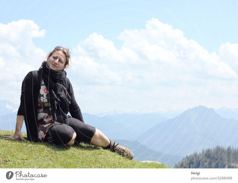 a woman is sitting on a mountain in fine weather, in the background you can see the Alps Human being Feminine Woman Adults 1 45 - 60 years Environment Nature