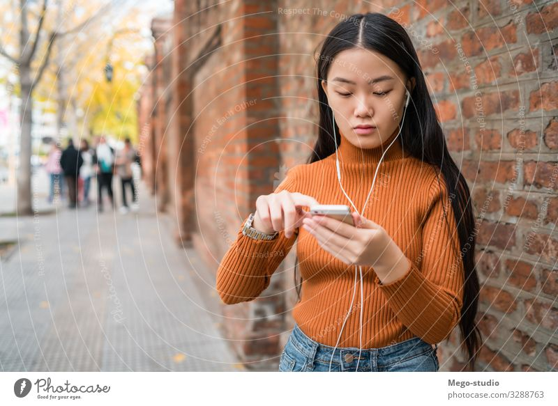 Asian woman using her mobile phone. Lifestyle Joy Beautiful Relaxation Decoration Telephone PDA Technology Internet Human being Woman Adults Street Fashion
