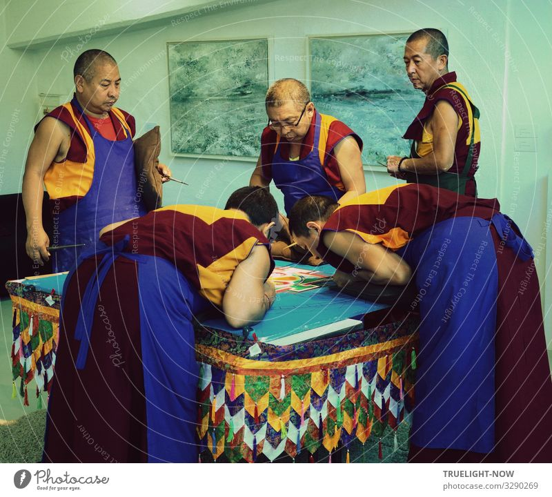 5 monks of the Tibetan exile monastery Sera-Jey during the ritual design of a sand mandala according to a traditional pattern with coloured sand grains