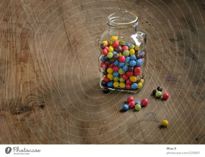 Jar Food Candy Chocolate Nutrition Small Delicious Sweet Multicoloured Chocolate buttons Storage tank Sphere Wooden table Colour photo Interior shot Close-up