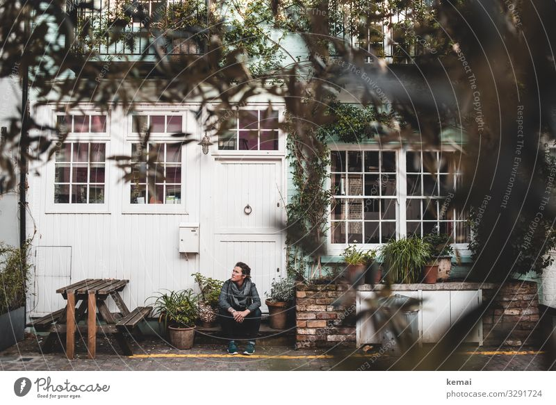 Woman sitting on stairs in front of the house urban Town Facade Window Sit Wait look Door front door Stage Table Bushes relaxed Break Relaxation Adults