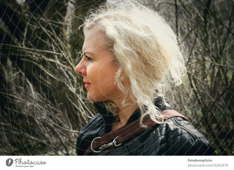 Portrait of a blonde woman with dog leash in front of bare bushes portrait Woman feminine Self-confident Face of a woman look expect expecting Blond Dog lead
