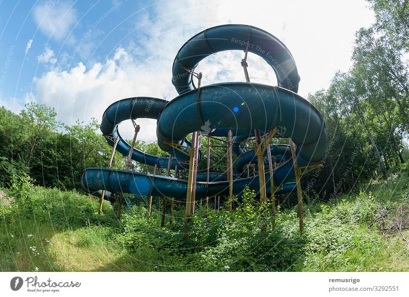 Abandoned water slide Relaxation Summer Sports Sky Clouds Tree Rust Looking Old Joy abandoned amusement slider sunflare Water slide Colour photo Exterior shot
