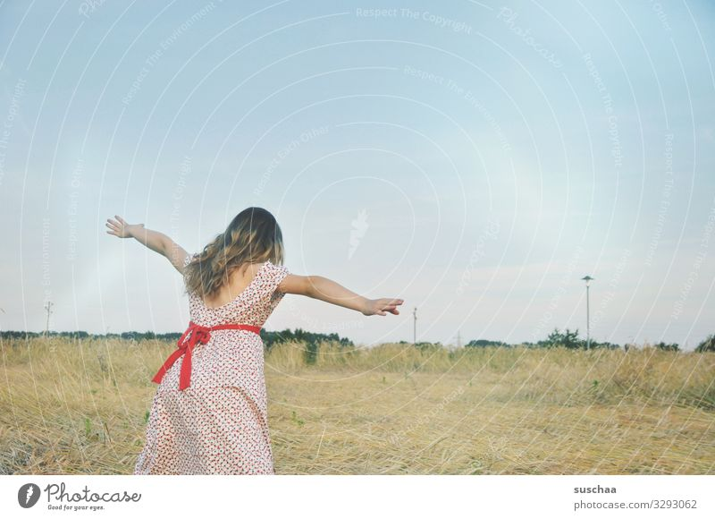 """girl in a straw field playing """"fly"""" Child Dress Exterior shot Nature Field Grain field Cornfield Landscape Summer Warmth Outstretched sleeves Bow Flying Playing"""