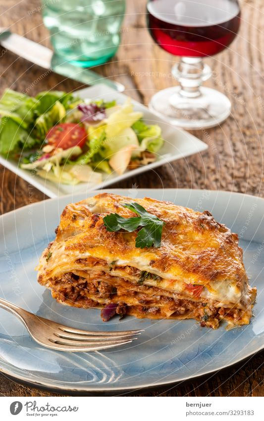 Lasagne on a plate Meat Cheese Vegetable Nutrition Dinner Crockery Fork Gastronomy Wood Fresh Delicious Parsley pasta Tasty disk Carbohydrates Bolognaise