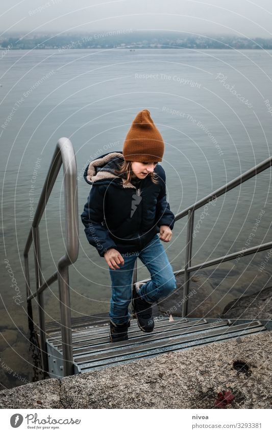 Boy at the lake in winter Boy (child) Child Lake zurich Stairs Water Winter cap winter jacket Movement Exterior shot Colour photo at I'm Day Nature chill Blue