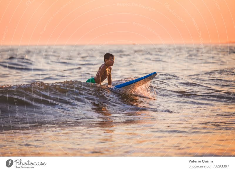 Surfing at Sunset Boy (child) 1 Human being 8 - 13 years Child Infancy Water Sky Horizon Summer Waves Beach Swimming trunks Joy Vacation & Travel surfing
