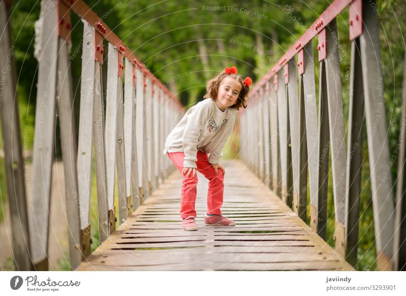 Cute little girl having fun in a rural bridge Joy Happy Beautiful Life Playing Child Human being Feminine Baby Woman Adults Infancy 1 3 - 8 years Nature Flower
