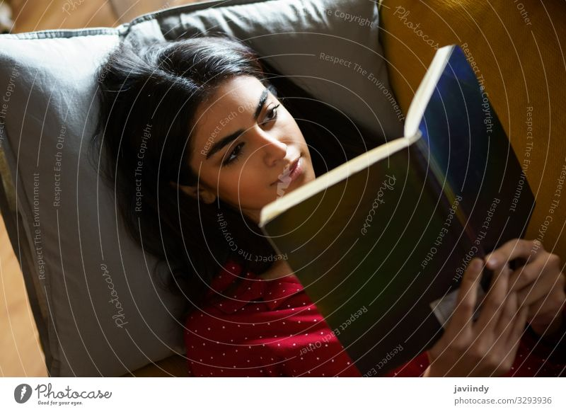 Persian woman at home reading on a couch Woman Human being Youth (Young adults) Young woman House (Residential Structure) Relaxation Joy Winter 18 - 30 years
