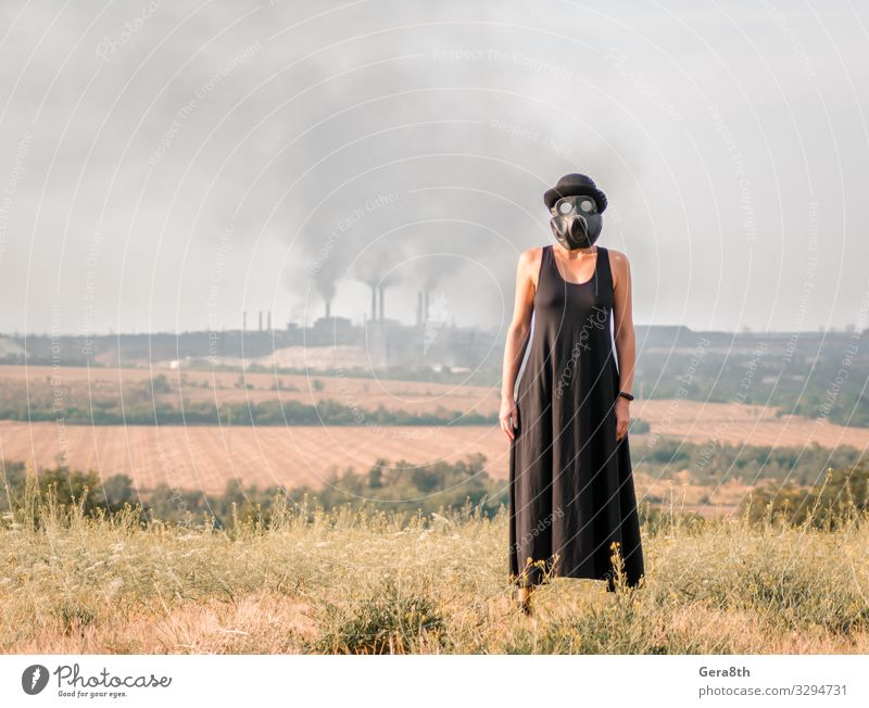 young girl in a black dress and gas mask Woman Human being Sky Nature Plant Landscape Black Adults Environment Natural Grass Protection Dress Hat Factory Pipe