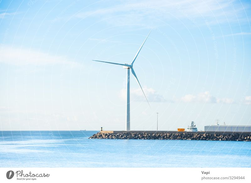 Windmill at edge of breakwater Ocean Waves Energy industry Wind energy plant Environment Nature Landscape Sky Clouds Horizon Coast Blue Green Black White