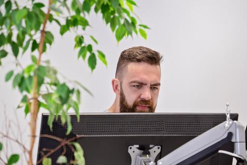 Bearded man works behind computer monitor in office Lifestyle Design Desk Table Work and employment Workplace Office Business Computer Notebook Screen