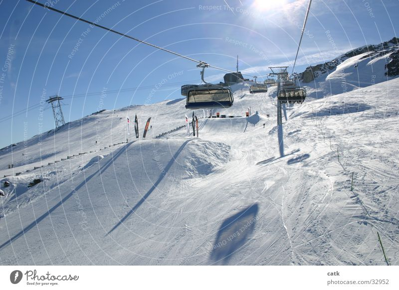 In the ski lift Vacation & Travel Sun Mountain Winter sports Skiing Ski lift Ski resort Skilift chair Ski run Sky Cloudless sky Beautiful weather Peak