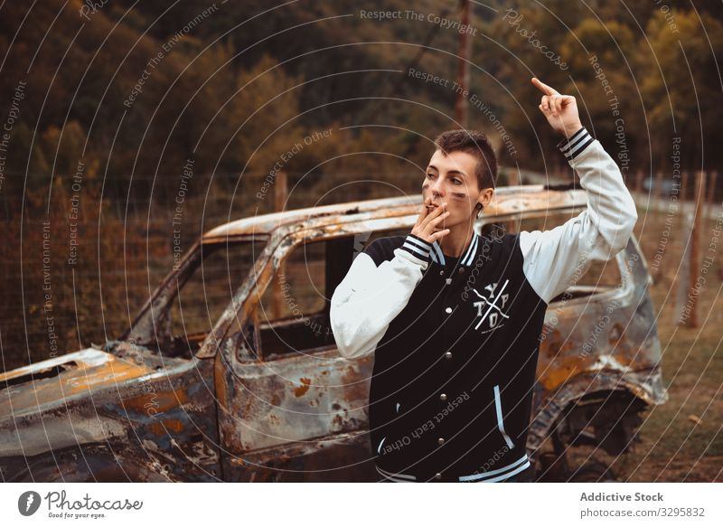 Woman with cigarette walking near burnt car woman smoke rebel rest rusty countryside young lean lifestyle freedom vehicle auto androgynous short hair subculture
