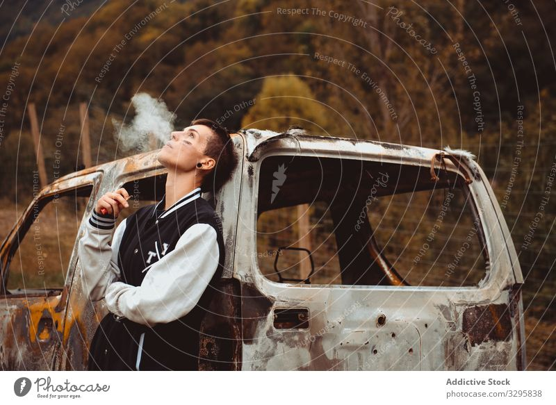 Young female smoking near damaged car woman cigarette smoke exhale rebel rusty countryside burnt young lean freedom vehicle auto androgynous short hair