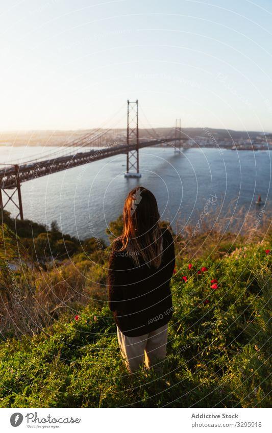 Unrecognizable female admiring bridge over river woman admire evening suspension modern sky cloudless portugal landmark architecture building structure