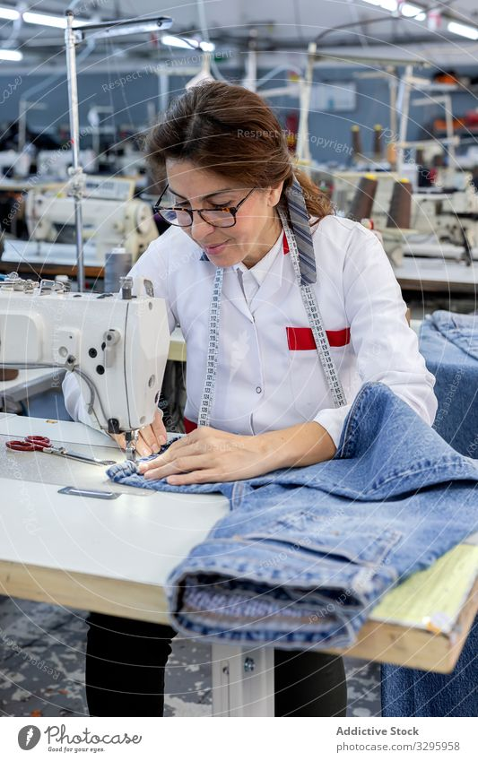 Woman's hands in textile factory sewing on industrial sewing machine. industry clothing manufacturing worker woman fabric pants blue jeans occupation production