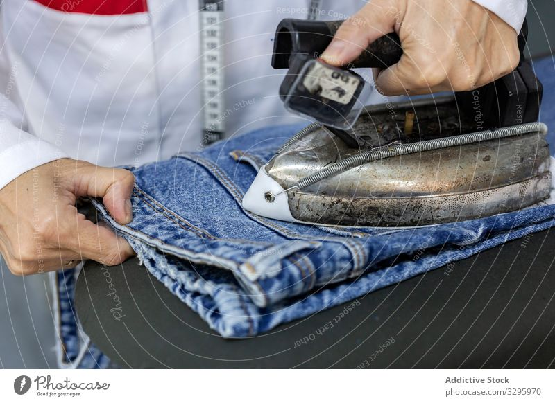 Woman's hands in textile factory ironing on industrial sewing machine. industry clothing manufacturing worker woman fabric pants blue jeans occupation