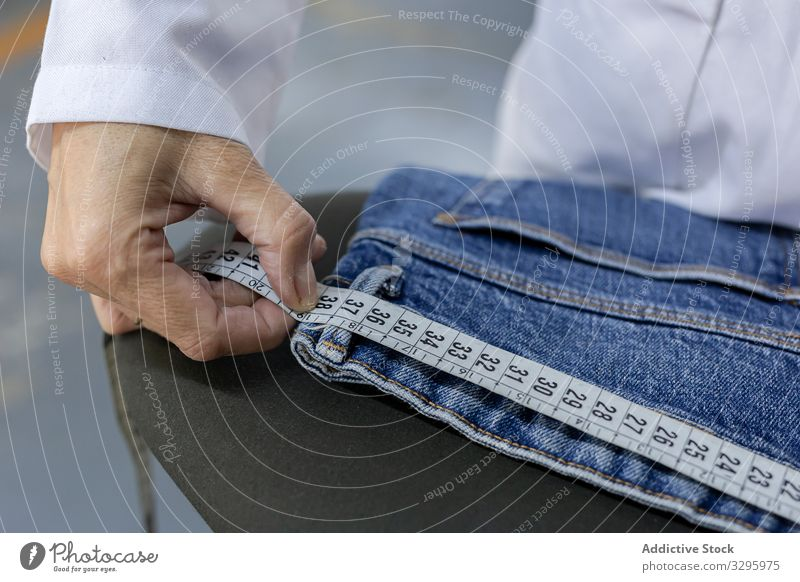 Working woman in textile factory checking industry clothing manufacturing worker machine sewing hands fabric pants blue jeans occupation industrial production