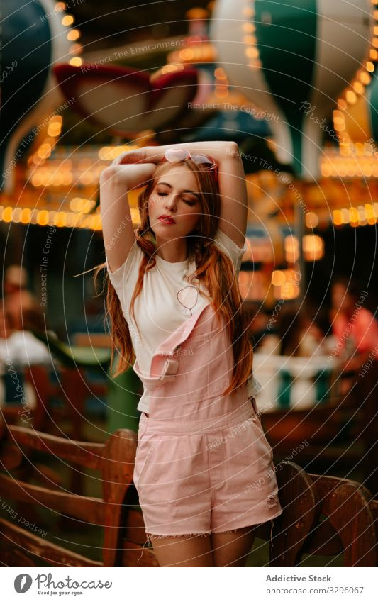Stylish teenage girl standing in amusement park woman style fashion teenager trendy sensual jumpsuit millennial relax enjoy young careless childish redhead