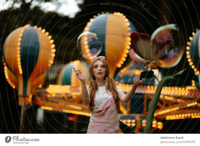 Teenage female playing with soap bubbles in amusement park woman girl teenager fun carefree playful enjoy style fashion trendy fashionable pure childlike young