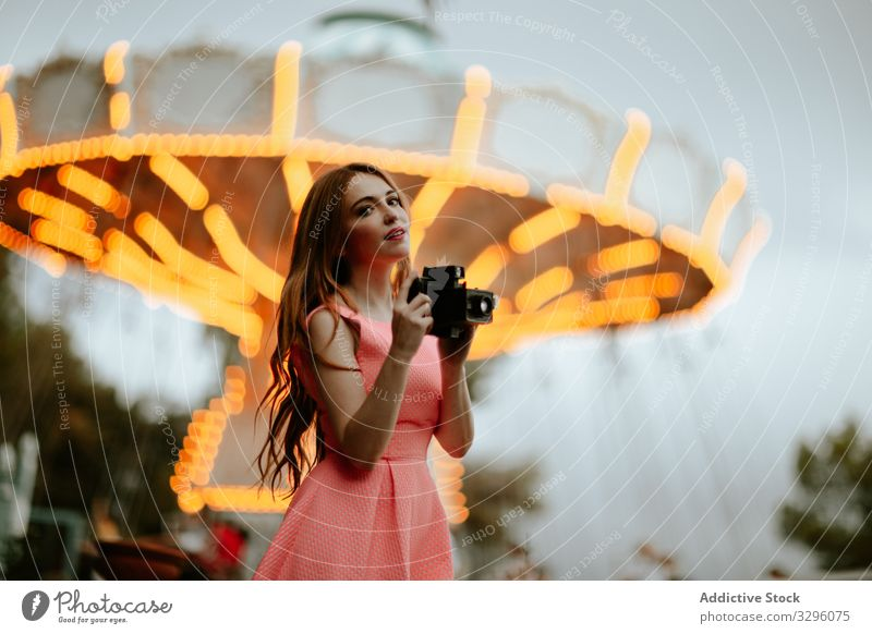 Millennial woman taking picture with camera in amusement park taking photo funfair trendy romantic dress pink teenager carousel millennial fashion style female